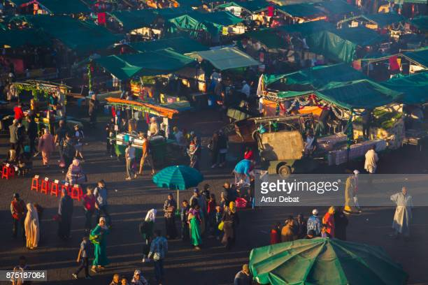 The bustle Jemaa El Fna square in the city of Marrakech with activity, street food market lights and people gathering, picture taken from elevated viewpoint during travel vacations in Morocco.