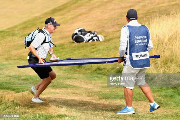 The caddie of Darren Fichardt of South Africa and a volunteer move an advertising sign on hole one during day four of the Aberdeen Standard...
