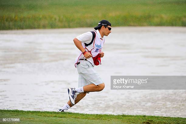 The caddie of David Pastore runs back to the drop zone after Pastore hit his second tee shot into the water on the 17th hole of the Champion Course...