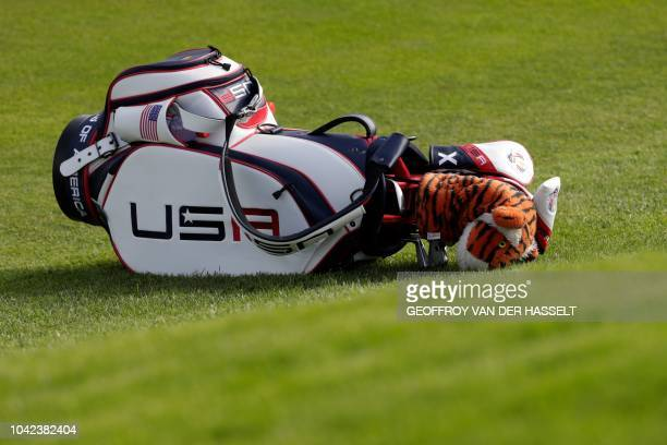 TOPSHOT The caddie of US golfer Tiger Woods lies on the ground during his fourball match on the first day of the 42nd Ryder Cup at Le Golf National...