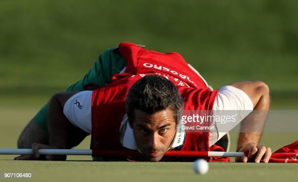 The caddy of Italian golfer Matteo Manassero known simply as 'Job' gets a worm's eye view of the line of a putt on the 16th green during the second...