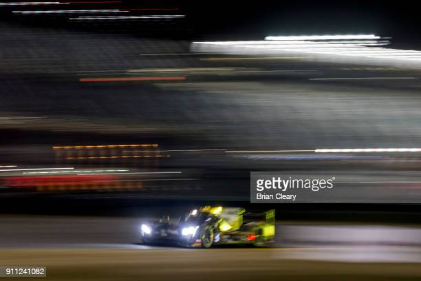 The Cadillac DPi of Joao Barbosa of Portugal Christian Fittipaldi of Brazil and Felipe Albuqureque of Brazil races on the track at night during the...