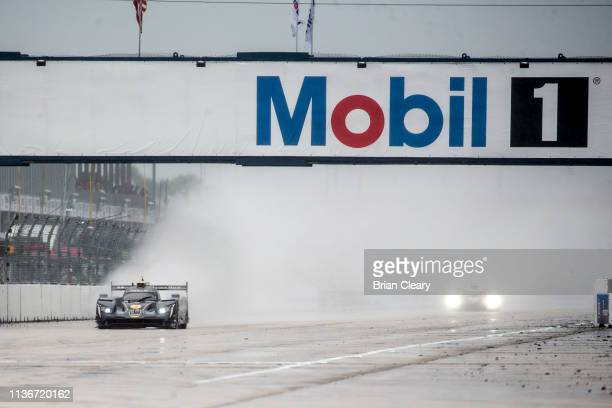 The Cadillac DPi of Joao Barbosa, of Portugal, Felipe Albuquerque, of Portugal, and Brendon Hatley, of New Zealand, races on the track in the rain...