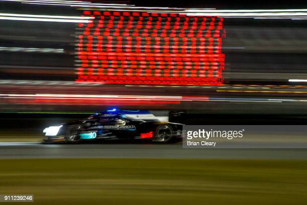 The Cadillac DPi of Jordan Taylor Ryan HunterReay and Renger van der Zande of the Netherlands races past a scoring tower at night during the Rolex 24...