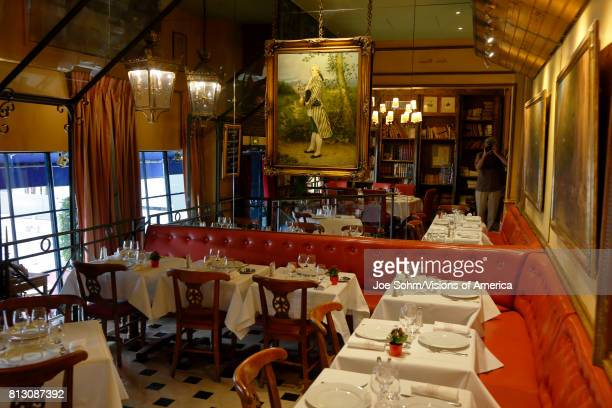The Cafe Procope interior in Paris with portraits of famous writers and revolutionary politicians Benjamin Franklin Jean Jacques Rousseau Robespierre...