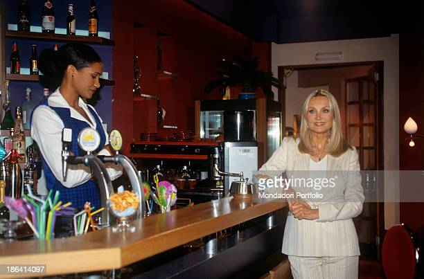 The Caffè Vulcano one of the soap opera set of Un posto al sole with Denny Mendez behind the counter and Barbara Bouchet leaning onf the countertop...