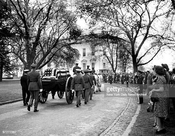 The caisson drawn by six white horses rolls into the White House grounds during Franklin D Roosevelt funeral procession