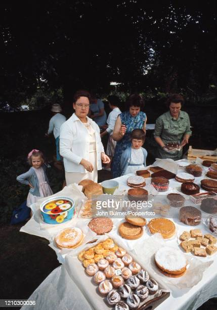 The cake stall and baking competition, with helpers and customers, during the church fete in the Rectory garden at Pembridge in England, circa June...