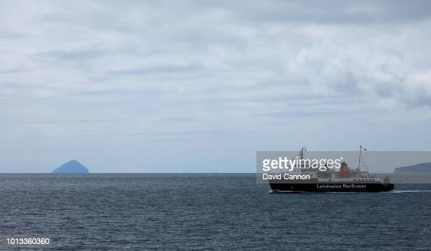 The Caledonian MacBrayne Car Ferry sailing out of the port of Brodick to Ardrossan on the Scottish mainland with the island of Ailsa Craig in the...