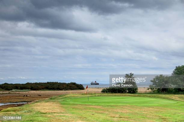 The Caledonian MacBrayne Car Ferry sailing out of the port of Brodick to Ardrossan on the Scottish mainland with the green on the par 3 15th hole at...