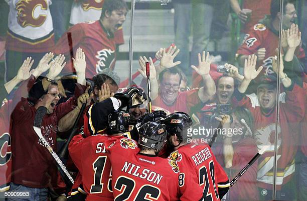The Calgary fans pound the glass as the Flames celebrate with Chris Simon of the Calgary Flames after he scored the first goal of the game against...