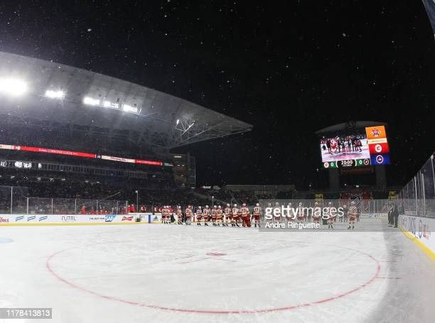 The Calgary Flames line up on the blue line before taking on the Winnipeg Jets during the 2019 Tim Hortons NHL Heritage Classic at Mosaic Stadium on...