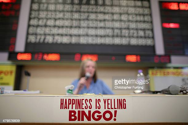 The 'caller' yells out numbers as people play Bingo at Carlton Bingo Hall in Orrell Park as the Chancellor George Osborne announces tax breaks for...
