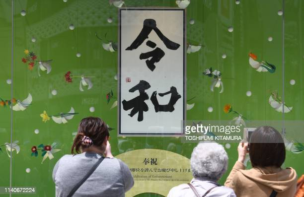 The calligraphy of Japan's new Reiwa era is on display on the shop window of a department store at Ginza shopping district in Tokyo on May 2 2019...