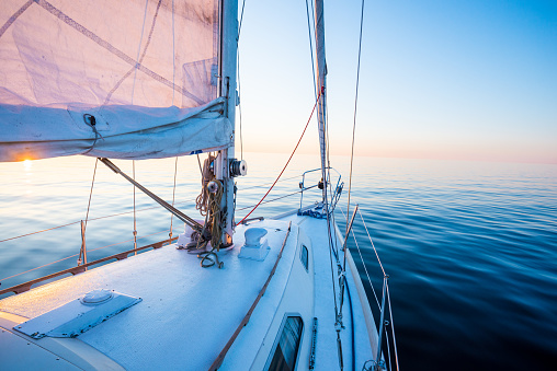 The calm water. White sloop rigged yacht sailing at sunset. A view from the deck to the bow, mast and the sails. Baltic Sea, Latvia 1172772859
