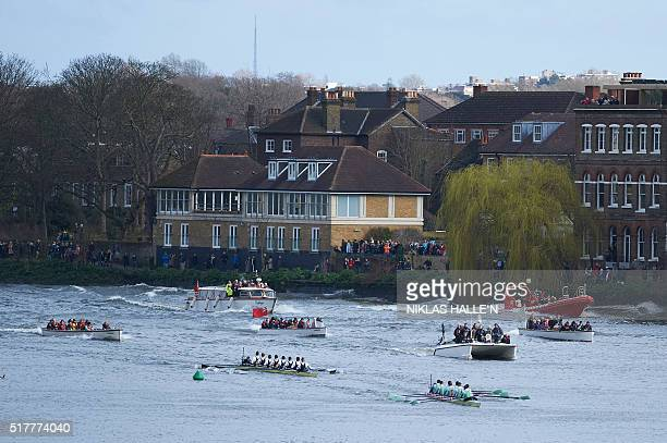 The Cambridge crew lead Oxford crew as they row in to toward the finish line with the flotilla following in the annual men's boat race between Oxford...