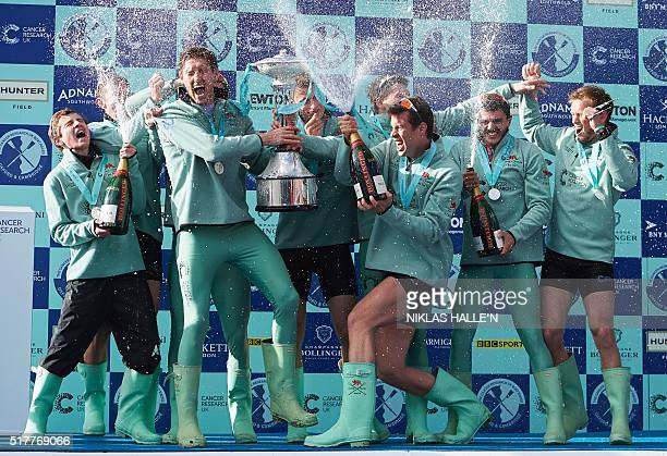 The Cambridge men's crew celebrate with trophy after winning the annual men's boat race between Oxford and Cambridge University on the River Thames...