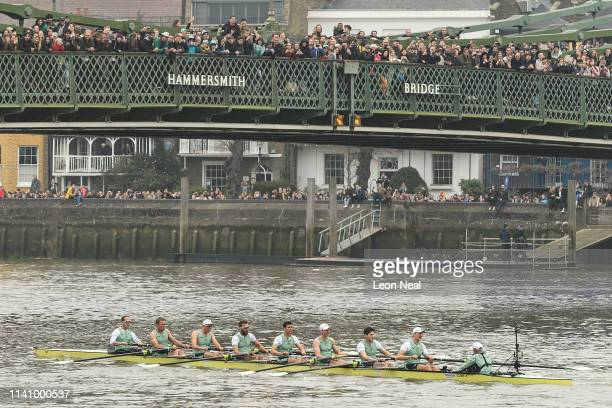 The Cambridge Men's team pass under Hammersmith Bridge as they head to victory during the Oxford versus Cambridge boat race on April 07 2019 in...