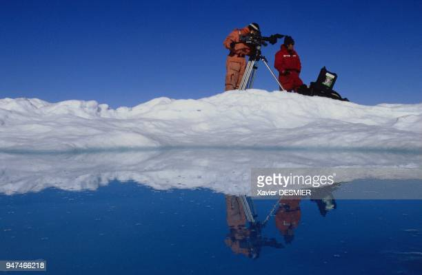 The cameraman Thierry Machado and his canadian assistant Stéphane Paillard watch and film a bowhead Whale when ice field melts in july between...
