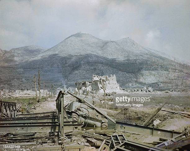 The Advance On Cassino May 1944 View of Cassino after heavy bombardment showing a knocked out Sherman tank by a Bailey bridge in the foreground with...