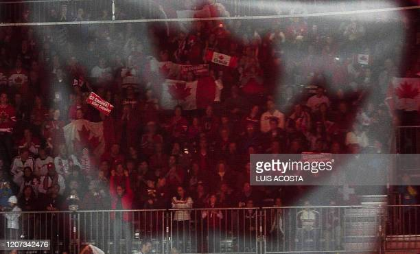 The Canada National Flag is reflected in glass over fans during the Women's Ice Hockey preliminary game between Switzerland and Canada at the UBC...