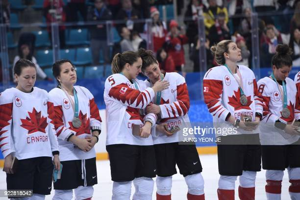 TOPSHOT The Canada team stands on the podium during the medal ceremony after winning the silver in the women's ice hockey event during the...