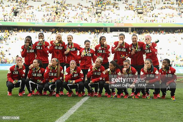 The Canadiam team pose with their bronze medals during the Women's Football Bronze Medal match between Brazil and Canada on Day 14 of the Rio 2016...
