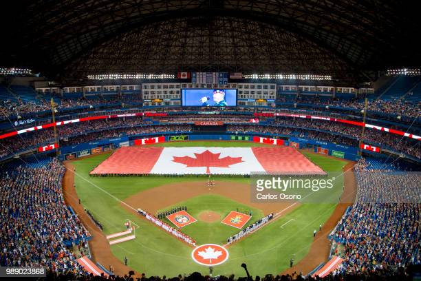TORONTO ON JULY The Canadian flag is seen during the anthems on Canada Day during the baseball game between the Toronto Blue Jays and the Detroit...