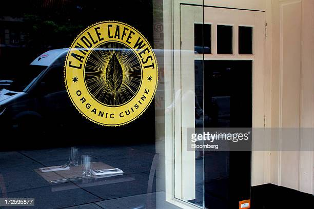 The Candle Cafe West logo is displayed on the restaurant's window in New York US on Monday May 27 2013 The vegan cafe serves tempeh vegetable cake...
