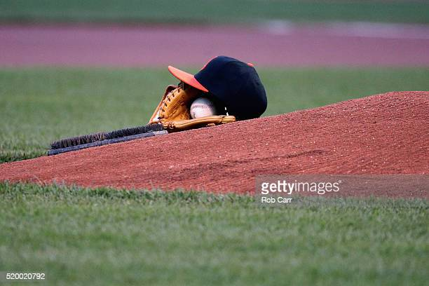 The cap and glove of starting pitcher Chris Tillman of the Baltimore Orioles sit on the mound during the national anthem before the start of the...
