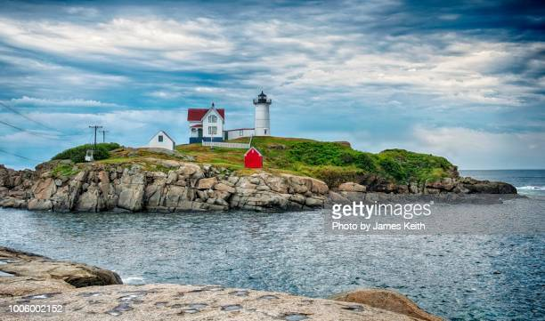the cape neddick lighthouse dates to 1879 and although now automated is still an active coast guard navigation aid. - rocky coastline stock pictures, royalty-free photos & images
