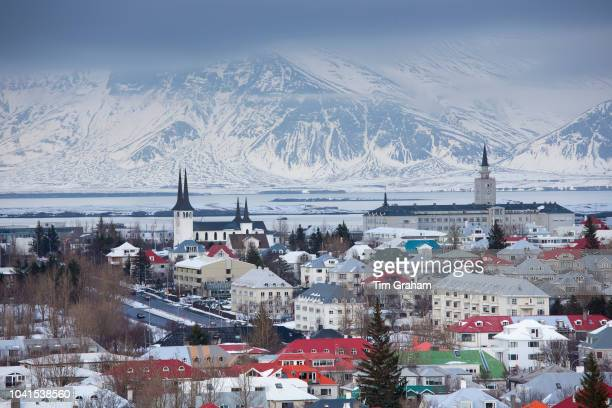 The capital city of Reykjavik with traditional bright coloured rooves and snow-covered glacier mountains, Iceland.