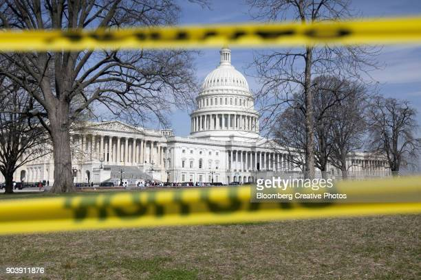 the capitol building stands behind caution tape - government shutdown stock pictures, royalty-free photos & images