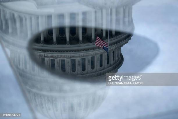 TOPSHOT The Capitol Rotunda is reflected in water as negotiations on a COVID19 economic bailout continue on Capitol Hill March 24 in Washington DC US...