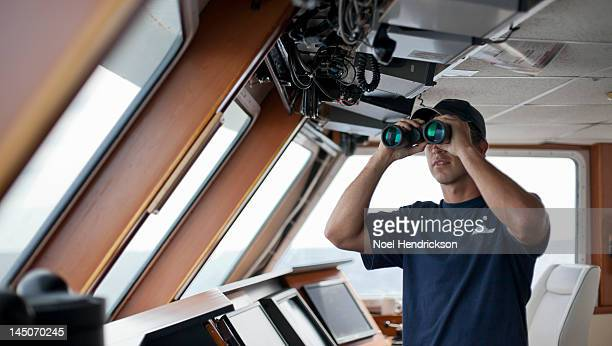 the captain of a boat looks out from the bridge - team captain stock pictures, royalty-free photos & images