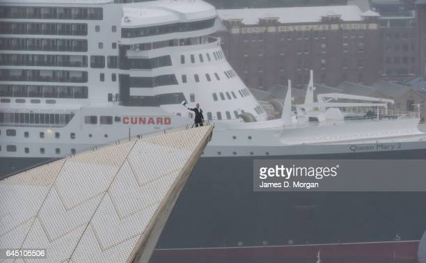 The Captain of Cunard's Queen Mary 2 Christopher Wells salutes Sydney high above the city on the top sail of the Opera House on February 25 2017 in...