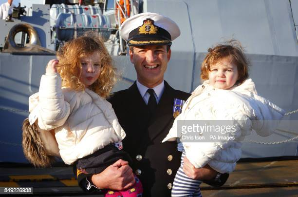 The Captain of HMS Diamond Commander Ian Clarke with daughters Rebecca three and Emilia 22 months after returning home to Portsmouth Royal Navy Base...