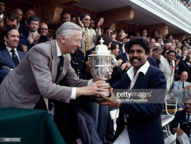 The captain of India Kapil Dev receives the Prudential World Cup Trophy from the Chairman of Prudential Assurance Lord Carr of Hadley after India's...