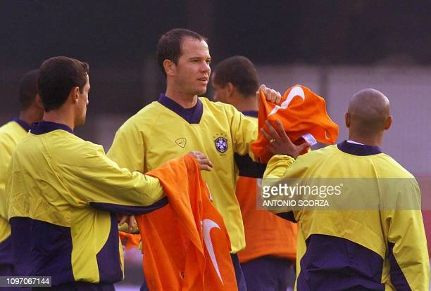 The captain of the Brazil selection team Antonio Carlos passes vests to his teammates Roberto Carlos and Belletti during the practice 25 July 2000 in...
