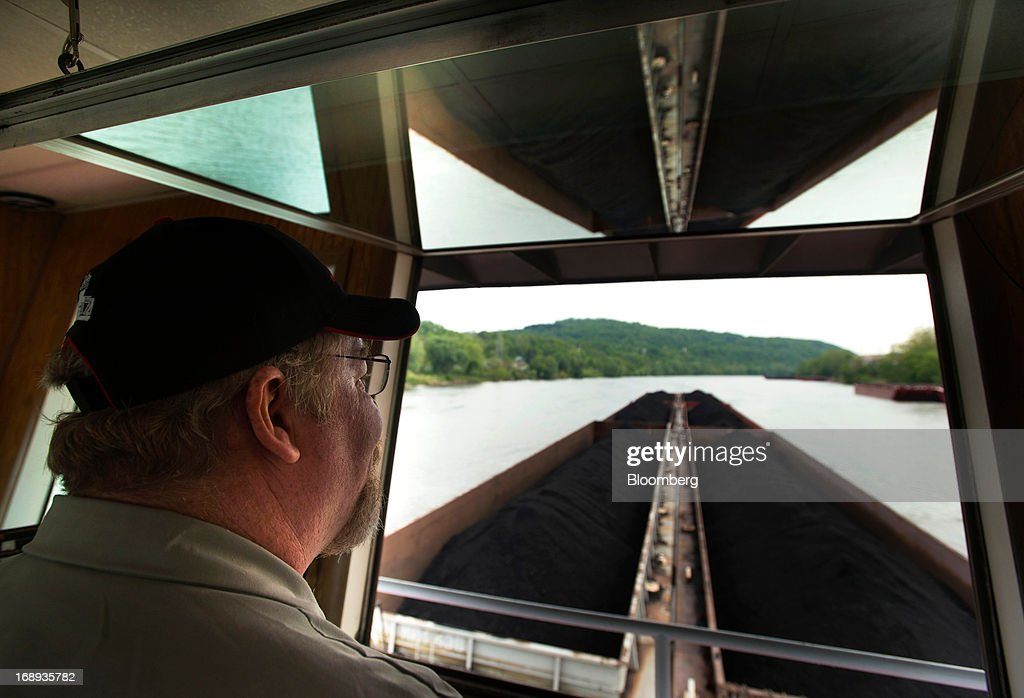 The captain of the Consol Energy Champion Coal tow boat looks out the window at his load of barges containing coal during transport down the Monongahela River, outside Pittsburgh, Pennsylvania, U.S., on Wednesday, May 15, 2013. Coal's prospects are improving after its share of U.S. power generation fell last year to 34 percent, the lowest since at least 1973, Energy Department data show. Hotter temperatures this summer that prompt American households to use more air conditioning will boost demand for coal and the railroads that ship it. Photographer: Ty Wright/Bloomberg via Getty Images