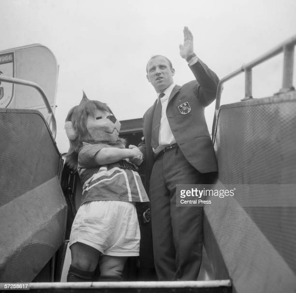 The captain of the West German football team Uwe Seeler posing with mascot World Cup Willie as he is boarding a plane during the 1966 World Cup in...