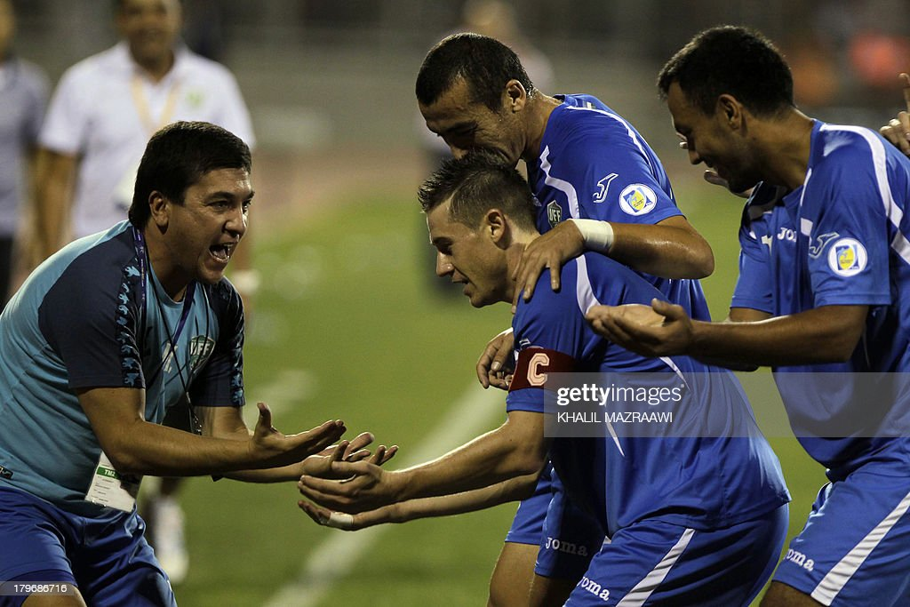 The captain of Uzbekistan's national team Server Djeparov (C) celebrates with his teammates and coach Mirdjalal Kasimov (L) after he scored a goal during their 2014 World Cup qualifier football match against Jordan at the King Abdullah international stadium in Amman on September 6, 2012. The match ended in a draw.