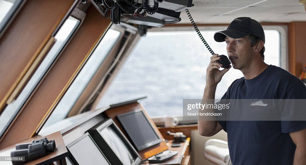 The captain uses a radio from the bridge of a boat : Stock Photo