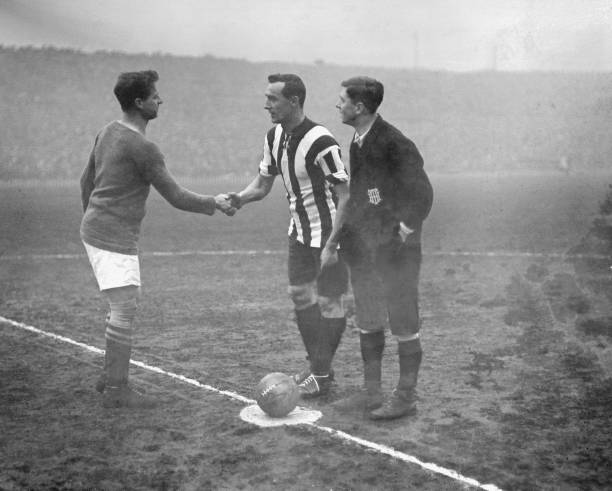 The captains of Chelsea and Sheffield United shake hands before the start of the FA Cup Final at Old Trafford, which United won 3-0, 24th April 1915.
