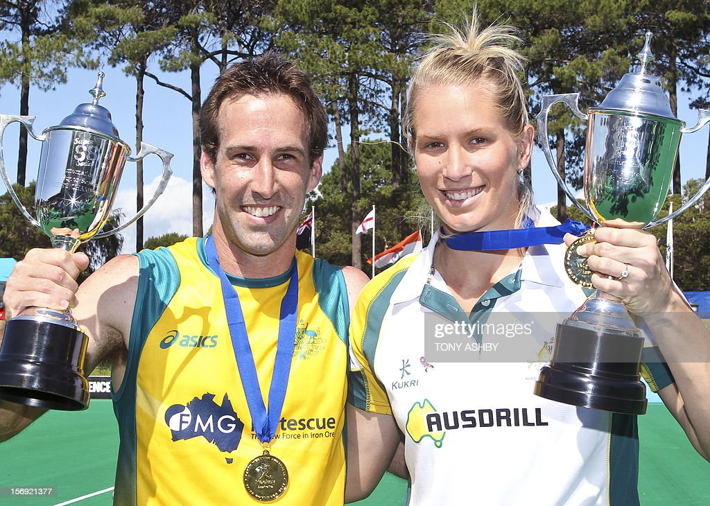 The captains of the final winning teams with their respective trophies, Liam De Young (L) of the Australian Wallabies and Jodie Schulz of the Australian Hockeyroos pose after the tournament on the final day of the International Super Series hockey tournament in Perth on November 25, 2012. AFP PHOTO / Tony ASHBY IMAGE
