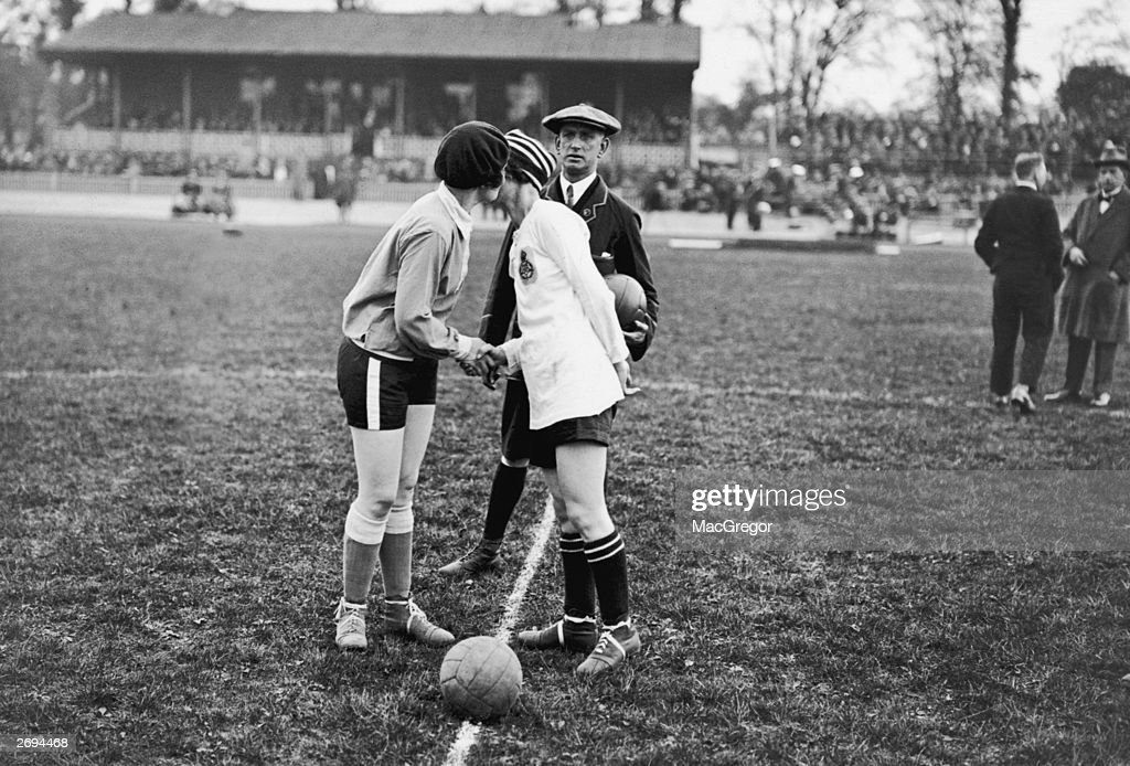 The captains of the French and English Ladies football teams, Carmen Pomies (left) and Florrie Redford, having a handshake and a peck on the cheek before the start of the England vs France Women's International Football match in aid of shipwrecked mariners, at Herne Hill, London, 12th May 1925.