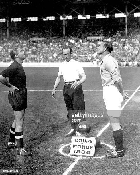 The captains of the French and Italian national soccer teams Etienne Mattler and Giuseppe Meazza watch the coin toss as Belgian referee Louis Baert...