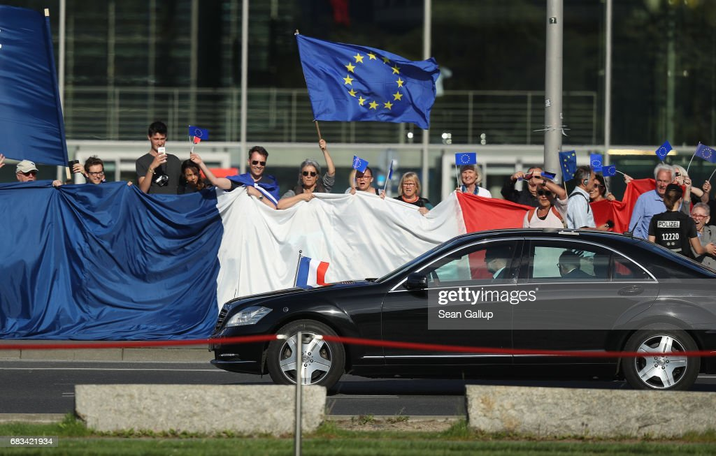 The car carrying newly-elected French President Emmanuel Macron drives past pro-European supporters with a giant French flag as Macron arrives to meet German Chancellor Angela Merkel chat the Chancellery on May 15, 2017 in Berlin, Germany. Macron is visiting Berlin only a day after being sworn in as president in Paris. While Macron and Merkel have both demonstrated an unwavering commitment to the European Union and Merkel strongly applauded Macron's election, they are likely to differ over Macron's desire for E.U.-issued bonds, a measure Merkel has strongly opposed in the past.