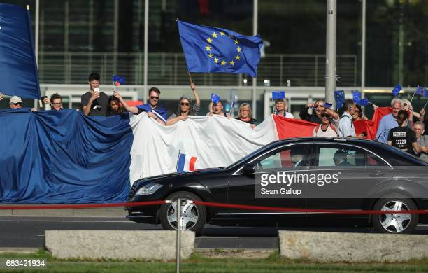 The car carrying newlyelected French President Emmanuel Macron drives past proEuropean supporters with a giant French flag as Macron arrives to meet...