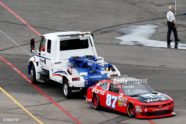 The car of Daryl Harr driver of the iWorld Chevrolet is towed to the garage after crashing during the NASCAR Nationwide Series Blue Jeans Go Green...